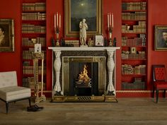 This rich red living room styled by Tim Gosling ofGosling Ltd., features anEgyptian RevivalFrench Empire fire fender. A painting of the Thames at night hangs over the mantle, which includesa statuette of Diana of Gabii andapair of Egyptian Revival Ormolu candlesticks fromGuinevere Antiques.