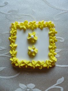 Sqaure shaped hand-decorated sugar cookie in yellow
