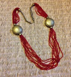 Handmade red seed bead necklace with metal medallion.
