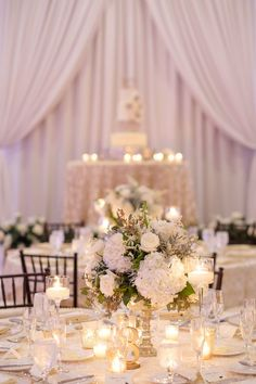Hotel Ballroom Gold and White Wedding Reception Round Table Decor with Short White Hydrangea and greenery Centerpiece with votive candles and blush linens, and white draping | St Pete Historic Wedding Venue The Vinoy