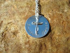 """Amazing Grace Hand-Stamped Necklace, Sterling Silver    This uplifting necklace features a 1"""" sterling silver circle pendant with the hand-stamped words """"Amazing Grace"""". Hanging in the center of the pendant is an elegant cross charm. Pendant comes attached to a sterling silver chain style of choice, which includes a 2"""" extension and our signature heart tag."""