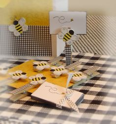 They are made from ordinary clothespins covered in scrapbook paper and adorable little bumble bee wooden cutouts glued in place...and check out the darling little cards to write the guests names on