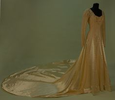 Full View TRAINED CREAM SATIN and LACE WEDDING GOWN. c. 1938. Long sleeve princess line lace with squared neckline, the skirt having satin gores, neckline and sleeve decorated with seed pearls, satin button and loop back and sleeve closures, hem stiffened with synthetic horsehair band, worn over satin strapless under- dress, matching lace headpiece with seed pearl trim.