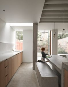 A concrete floor merges with seating inside and outside this rusted steel and glass extension to a Victorian-style house in west London, designed by local architecture studio McLaren Excell
