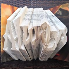 One-of-a-kind book art created by meticulously folding each page so that the book sculpture reflects the word, Always. The book is Harry Potter