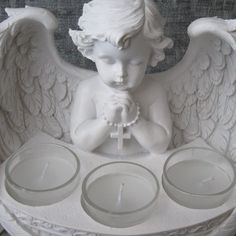 This beautiful cherub tea light holder is a perfect addition to your home or as a very thoughtful gift. This product is made from resin and it is finished with a soft white effect. It has three tea light holders and it is surrounded by elegantly detailed Angel wings.