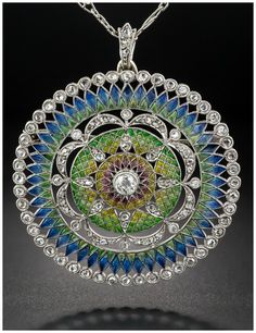 A colorful antique Belle Epoque plique-a-jour enamel pendant brooch with diamonds. - This piece dates to the year 1900 and features translucent plique-a-jour enamel in shades of blue, green, yellow and pin/red accents with sweeps of diamonds and gorgeous openwork. It's a pendant, but also features a pin fitting for wear as a brooch. In white gold.