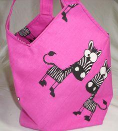 Da staunt das Zebra. Die Tasche ist so genäht, dass sie alleine stehen kann, um die Dinge, die man mitnehmen will, auch einpacken zu können. Die pinkfarbene Baumwolle ist doppelt genäht. Daher kann sie von beiden Seiten genutzt werden. Von den Kindern ist sie auch als Schultertasche zu tragen.