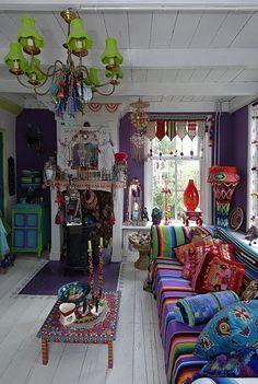 sala decorada no estilo boho chic, bohemiam chic com sofá de estampa colorida e almofadas estampadas coloridas, mesa de centro colorida, lustre colorido, enfeites de teto e parede