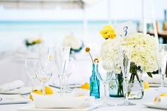 Blue vases w/ wildflowers, on burlap/ lace  Photography by Robert Rios Photography / weddings.robertrios.com