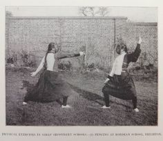 A vintage black-and-white photograph taken around 1905 and showing two schoolgirls demonstrating some fencing exercises The picture is captioned