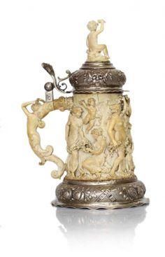 CHOPE, Allemagne fin XIXème En ivoire richement sculpté en ronde bosse de bacchanales entourant un satyre, la prise sculptée d'un putti, sur montant un couvercle en argent repoussé à charnière, sommé d'un putti en ivoire, l'anse décorée d'une cariatide finement sculptée. Base circulaire en argent repoussé d'un décor de fruits. Poinçons. Hauteur : 26 cm, Diamètre : 13,8 cm
