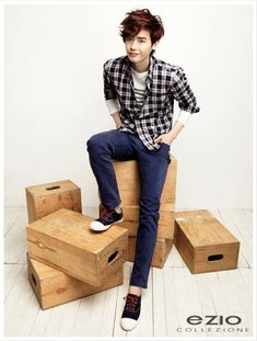 Lee Jong Suk in dark blue jeans with blue and red plaid button down over long sleeve shirt.