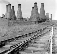 A pottery works with its forest of bottle kilns bordering a railway line in Stoke-on-Trent. Bottle kilns have a relatively short working life of about 30 years, so were constantly rebuilt. Due to recent changes in the industry, few of these distinctive monuments survive in the area.