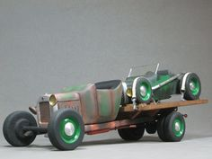 Nice hand made wooden model of an early flatbed truck hauling an open wheel roadster.