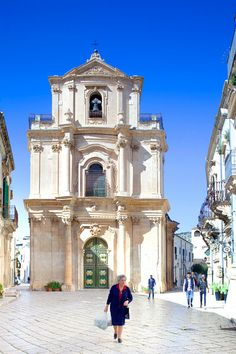 Italy, Sicily, Scicli, Elderly Sicilian woman walking in front of church of San Giovanni in one of main squares in historic center