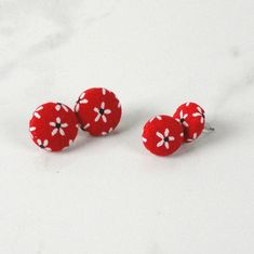 Bright and summery, these pretty red button earrings with white daisies will remind you of summer. Perfect with a sweater and jeans or a summer dress, these cute covered button earrings are versatile, lightweight and comfortable with a stylish retro look. Add some retro to your