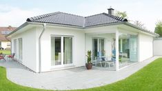 Fingerhut Bungalow Einfamilienhaus weiß verputzt schwarzes Dach weißer Dachüberstand bodentiefe Fenster Terrasse