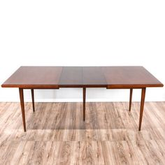 This mid century modern dining table is featured in a solid wood with a glossy cherry finish. This dining table has tapered legs, a removable glass table top and 2 leaf inserts. Perfect for casual and formal dining! #midcenturymodern #tables #diningtable #sandiegovintage #vintagefurniture