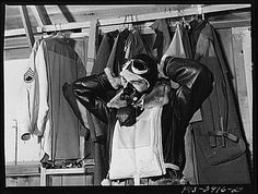 """One of the """"Flying Sergeants"""" dons his oxygen apparatus for high altitude flying. Immediately over his heavy flying suit is his """"Mae West"""" life preserver, which is easily inflated. The airman was photographed by Russell Lee in May 1942 at Lake Muroc, California. Life preservers were commonly nicknamed """"Mae West"""" because, once inflated, it appeared as physically endowed as actress Mae West."""