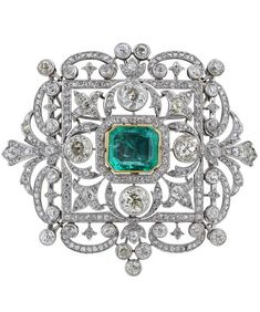 AN IMPRESSIVE EARLY 20TH CENTURY PLATINUM,EMERALD & DIAMOND BROOCH, cased by Garrard circa 1920. Of fleur-de-lys cluster design, gold collet-set with a step-cut emerald of Colombian origin estimated to weigh approximately 9cts, within a square openwork frame, highlighted at each corner with 4 collets, each set with a cushion-shaped diamonds, with a similarly set surround, original green leather fitted case, initialled R.L beneath a coronet.