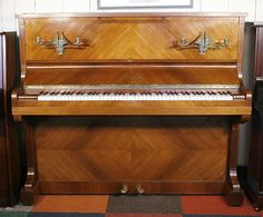 A 1927, Elcke upright piano with a quartered walnut case and brass candlesticks at Besbrode Pianos £1995