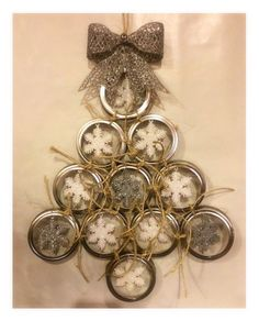 This unique Mason Jar Lid Wreath with matching ornaments is unique decor for the holidays. Style is a little bit country and a little bit Rock and Roll! Excellent piece for your entry door or as wall decor within your home. This handmade tree shaped door hanger is constructed from 11 silver Mason jar lids tied together with natural tone rough jute twine. Each ring has a sparkling silver or white snowflake hanging in its center. These are attached to the Mason jar rings with translucent…