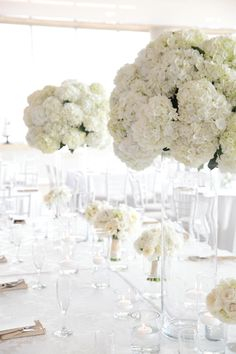 Mounds of white hydrangea perched atop tall cylinder vases with bride and bridesmaid bouquets down the center - Photographed by Allison Kuhn Photography.