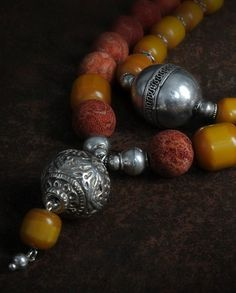 two necklaces, the longer having an old Indian silver bead and strung with vintage trade 'amber' and rough sponge coral. The inner necklace has a large Turkoman focal bead and is strung on vintage trade 'amber' with Afghani silver beads.