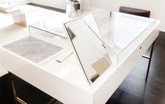 A custom white lacquer and polished brass jewelry case features marble trays and flip-up mirrors that also conceal ring sizers and additional inventory when not in use.