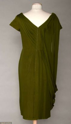 """MADAME GRES CHIFFON EVENING DRESS, 1960 Olive green fitted sheath w/ cap sleeves, pleated & draped neckline, pleated sash on front right side, lined in gray silk taffeta, labeled """"Gres, 1 Rue de la Paix, Paris"""". Back"""