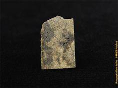 Tranche de 1,18g de lamétéorite martienne NWA 8656, trouvée dans le désert du Sahara, donnée par la sociétéLabenne Météorites(#83450 ; 1.8 x 1.1 x 0.2 cm).