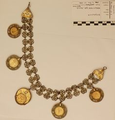 After conservation treatment. Note various shades of colour (pale and warm yellow and bronze paint on coins).  Woman's necklace or head ornament in gilded metal; a double chain formed of pairs of filigree rosettes with an applied lozenge at the join, ending in triangular filigree clasps with hook and eye fittings, each set with a red glass stone and a further applied lozenge. From the lower row of rosettes are suspended five coins of Peter II of Yugoslavia (1934-45) all dated 1938: two 50…