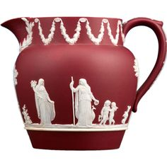 Wedgwood Crimson Jasper Pitcher  England  Circa 1920  This marvelous Wedgwood jasper dip bas-relief jug displays the rare and highly prized crimson color. Crimson jasper pieces were only created for a short period of time by Wedgwood during the 1920s, and they are highly collectible.