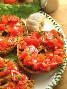 Friselle pugliesi al pomodoro, aglio e basilico: tipici taralli di grano duro cotti in forno e fatti biscottare, conditi in modo sano, semplice e genuino.