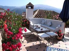 A tiny roof terrace in Andalucia, Spain, simply furnished with bright lipstick-red Oleander in the foreground.