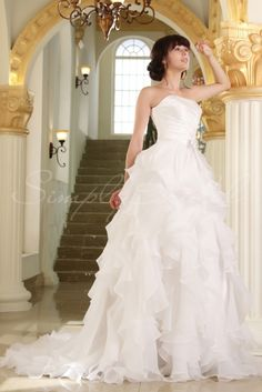 Wedding Dress by SimplyBridal. A ball gown silhouette crafted with romantic white satin organza ruffles that billow to the floor. The strapless bodice is gently pleated and features a straight neckline. A beaded bow sits at the waist. Allow the full ruffled skirt to drape you in luxury. USD $719.99