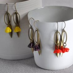 Longleaf Bell Flower Earrings from ArtySmartyShop.com These dainty hanging leaf earrings made from antiqued brass and a pretty  bell flower Czech glass bead, are inspired by the Irish countryside and turned into a contemporary piece in our Dublin studio where we handcraft each of our beautiful pieces. Whimsical and playful, we hope to create individual pieces for everyday wear. Ideal for summer fashion.  Each pair comes boxed in one of our artysmarty boxes.  #ArtySmarty #fashion #accessories Leaf Earrings, Flower Earrings, Handmade Jewellery, Earrings Handmade, Bold Fashion, Czech Glass Beads, Dublin, Antique Brass, Countryside