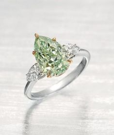 A COLORED DIAMOND RING ~ Set with a modified pear-shaped fancy intense green diamond, weighing approximately 3.51 carats, flanked on either side by a pear-shaped diamond, mounted in platinum