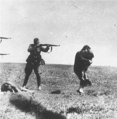 A mother holding her child close just before being killed by a Nazi Officer