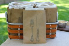Creative Backyard BBQ decoration ideas! Use stamped paper bags to hold your silverware and napkins. Put in a cute container - grab and go! #BBQ