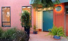 Linda entrada de uma casa, com cores fortes mas combinando maravilhosamente. Porta de madeira e janelas de vidro.