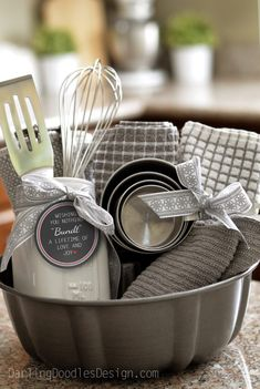 """Bundt Pan Gift Idea and Printable Tag - This gift has a bundt cake pan, dishtowels, dishcloths, measuring cups, kitchen utensils, and a cute mason jar.  You could also put in a boxed cake mix and frosting, spices like vanilla or cinnamon, toothpicks and cupcake liners, etc.  Anything """"baking"""" will totally fit!"""
