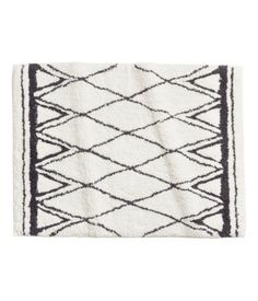 Natural white/patterned. Rectangular bath mat in jacquard-weave cotton fabric with non-slip protection at back.