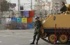 Soldiers stand guard by an armored vehicle in front of the Presidential Palace in Cairo, Egypt, Monday, Dec. 10, 2012. The Egyptian military on Monday assumed joint responsibility with the police for security and protecting state institutions until the results of a Dec. 15 constitutional referendum are announced. (AP Photo/Petr David Josek)