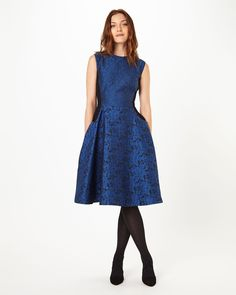 The fit and flare shape of this dress gives it a wonderful feminine silhouette that is made even more flattering by the side panels running down the bodice and waist. Using two complementing jaquard fabrics, this is an evening dress guaranteed to make you feel as good as you look.