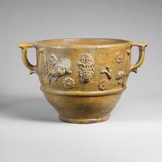The sides of this very large drinking cup are decorated with various appliqués, including heads, sea monsters, rosettes, and leaves