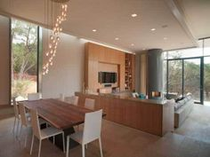 This modern home in Austin has tile flooring, a wooden dining table with simple white seating, built in open shelving and cabinetry, a circular fireplace and a tiered light fixture.