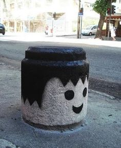 street art. turning pieces of the streets into pieces of fun art. cement curb divider into lego head