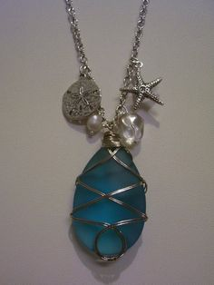 Blue sea glass pendant, freshwater pearl bead, silver sand dollar pendant, crystal bead, and a cute starfish.    The perfect beach comber necklace!  SOLD